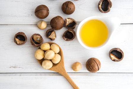 The Macadamia Nut Oil and peeled macadamia nut   on white table , ?use for Healthy Skin and Hair and Natural Healing Oil Treatment , overhead and top view Zdjęcie Seryjne - 85708004