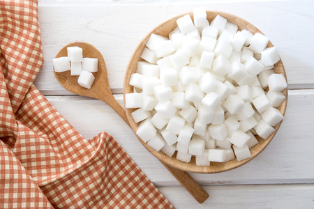 Close up the sugar cubes  in wooden bowl on  table , top view or overhead shot Stock Photo