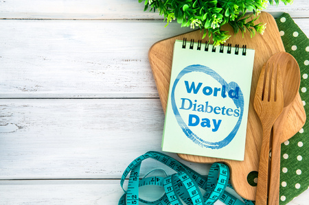 Bloc-notes avec texte de la Journée mondiale du diabète sur une planche à découper avec une fourchette et une cuillère en bois et ruban à mesurer sur un tableau blanc, Journée mondiale du diabète le 14 novembre Banque d'images - 88851267