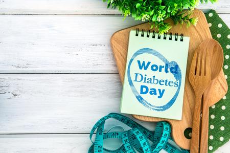 Kladblok met Werelddiabetes dag tekst op snijplank met houten vork en lepel en het meetlint op witte tafel, Diabetes werelddag op 14 november aanmoedigen voorlichting campagne achtergrond concept