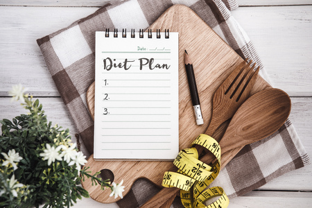 Line Notepad with Diet Plan list text  on chopping board with wooden fork and spoon and measuring tape on white table , recipes food or diet plan for healthy habits shot note background concept Stock Photo