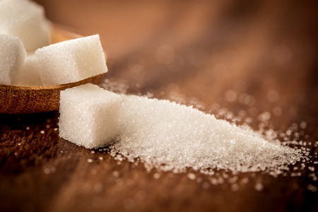 Close up the sugar cubes and cane in wooden spoon on the table ,retro color tone Stock Photo