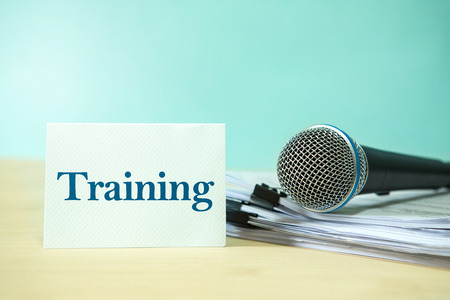 Close up Microphone on paper document with Training  text, concept of speaker or teacher preparation to speak in seminar class room Stock Photo