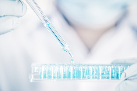 Close up a scientist working in laboratory to analyze blue extracted of DNA  molecules in micro tube plate , clinical or science testing analysis concept