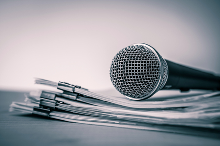 Close up Microphone with paper document , concept of speaker or teacher preparation to speak in seminar class room