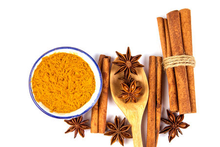Close up brown cinnamon stick and powder with star anise spice in wooden spoon isolated on white background  Stock Photo