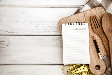 Notepad on chopping board with wooden fork and spoon  on white table , recipes food or diet plan for healthy habits shot note background concept