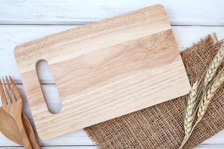 Schneidebrett und Tischdecke mit Holzgabel und Löffel auf weißem Tisch, Rezepte Nahrung für gesunde Gewohnheiten Schussnotiz Hintergrundkonzept Standard-Bild