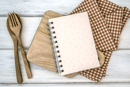 lined book notepad paper on chopping cutting board and tablecloth with wooden fork and spoon on white table , recipes food  for healthy habits shot note background concept