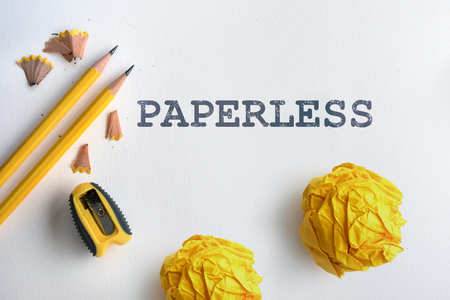 PAPERLESS text and Yellow pencil and yellow crumpled paper with shaving on white drawing watercolor paper  Stock Photo