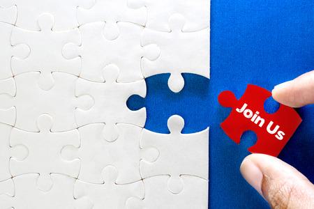 Schließen Sie herauf Teil des weißen Puzzles mit Join Us-Text, Konzept des Erfolgs der Geschäftsherausforderung mit Teamarbeit Standard-Bild