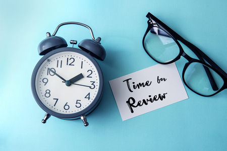 Time concept with paper note of Time fo Review message , alarm clock with reading eyeglasses decoration on blue background Archivio Fotografico