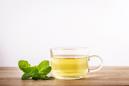 Close up glass cup of mint tea with green fresh peppermint leaves , relaxation and healthy drink Фото со стока