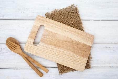 Schneidebrett und Tischdecke mit Holzgabel und Löffel auf weißem Tisch, Rezepte für gesunde Gewohnheiten, geschossenes Hintergrundkonzept Standard-Bild