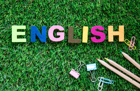 colorful ENGLISH word cube on green grass yard  background ,English language learning concept