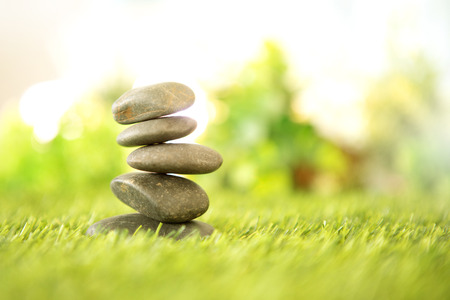 balance  with a pyramid of stone on fresh nature green grass  , spa meditation or well-being with zen concept Imagens