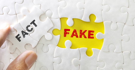 Close up piece of white jigsaw puzzle with FACT FAKE text , concept of fake news or information
