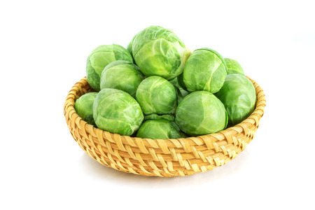 Fresh green brussel sprouts vegetable in basket on white background