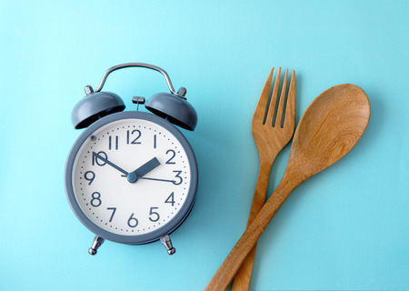 Time to lose weight , eating control or time to diet concept , alarm clock decoration on blue background Stock Photo