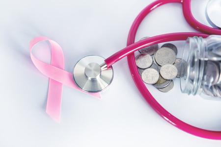 Brustkrebs-Krankenversicherung und Geldeinsparung für das Konzept der Krankenversicherung im medizinischen Gesundheitswesen, Münzgelddose mit Stethoskop und rosafarbenem Band auf weißem Hintergrund Standard-Bild