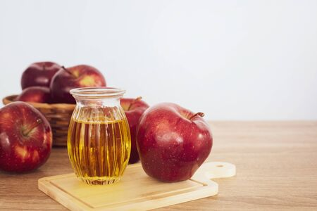 Nahaufnahme von roten Apfelfrüchten und einem Apfelessigsaft, hilft beim Abnehmen und reduziert Bauchfett, gesundes Essen