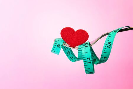 Diet for weight loss , measuring tape with fork with red heart shape for take care healthy eating concept 写真素材