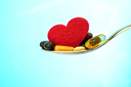 colorful medical supplement and drug pills with red heart in spoon , pharmaceutical cardiology drugs for heart health care disease concept 写真素材
