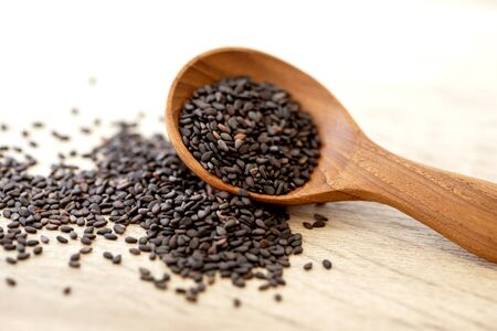 organic Black  sesame seeds in wooden spoon, healthy food for reductions in both systolic and diastolic blood pressure