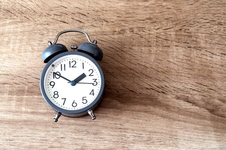 Alarm clock on brown wooden background, time management concept