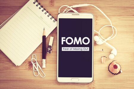 FOMO, Fear of missing out text on Smart phone with Blank notepad and pencil on wooden table