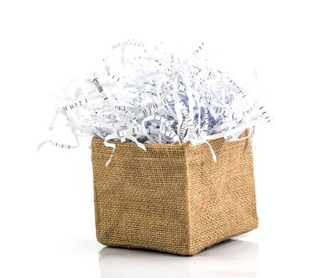 shredded paper waste in burlap bag box on white background