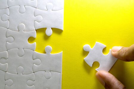 Close up piece of white jigsaw puzzle, concept of business challenge completion with teamwork
