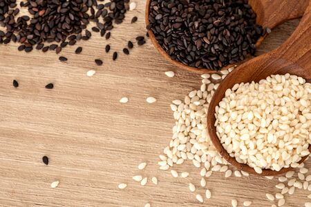 organic Black and White sesame seeds in wooden spoon, healthy food for reductions in both systolic and diastolic blood pressure