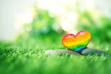 rainbow colorful watercolor of LGBT heart  on green nature grass background