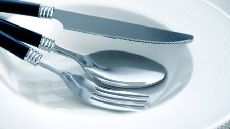 close up dinning the silverware fork, spoon and knife with dish on white background and text space