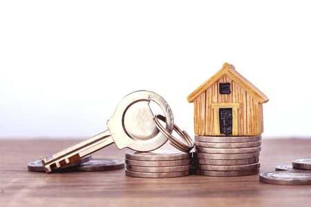 Close up a house model place on stacking of money coin for home mortgage and loan ,  refinance or property investment concept Stock Photo