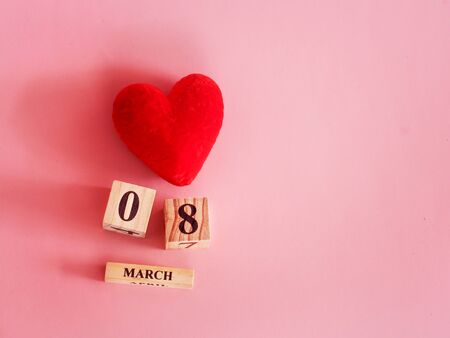 decoration of wooden date blog cube for 8 March , international women's day with red heart shape on pink for celebration concept