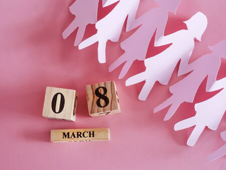 decoration of wooden date blog cube for 8 March , international women's day with paper craft women shape on pink for celebration concept