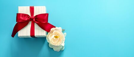 gift box with red bow on blue background . Happy Father's or Mother's or Women 's  day celebration concept