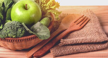 close up green apple with mixed green vegetable in a basket and wooden fork and spoon for healthy organic green food concept