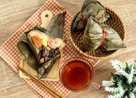 Close up Zongzi or rice dumpling on wooden table with Chinese tea in Dragon Boat Festival, Asian traditional food