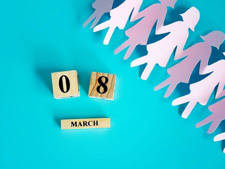 decoration of wooden date blog cube for 8 March , international women's day with paper craft women shape on blue for celebration concept