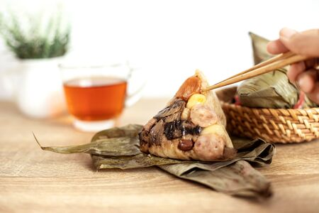Close up Zongzi or rice dumpling on wooden table with Chinese tea in Dragon Boat Festival, eating zongzi by chopstick Asian traditional food