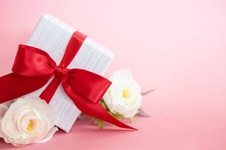 gift box with red bow on pink background . valentine 's or Mother's or Women 's  day celebration concept