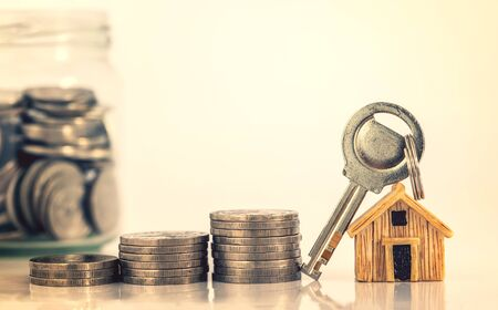 Close up house model place on a stacking of money coin for home mortgage and loan ,  refinance or property investment concept