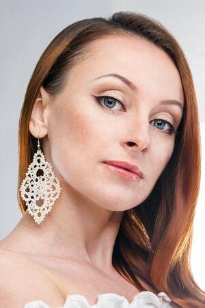 白いレースのイヤリングを持つ高級女性 写真素材
