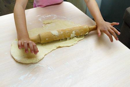 子は、テーブルの上の shortbread のこね粉をロールバックします。 写真素材