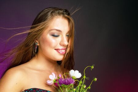 embarrassment: Young beautiful woman with flowers smiling shyly on a purple background. Stock Photo