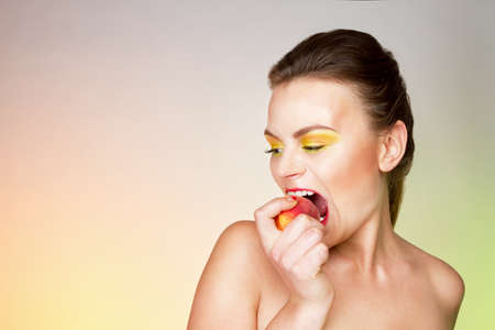 Young woman with yellow shades on the eyes emotionally bites peach.