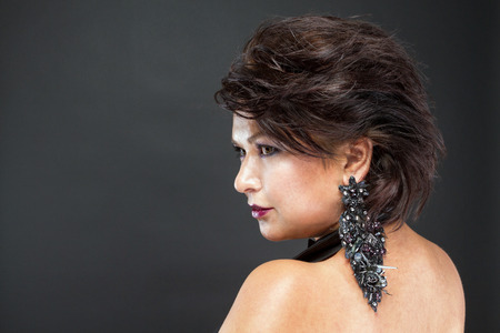chic woman: Profile of a woman with beautiful hair and laid chic black earrings. Stock Photo